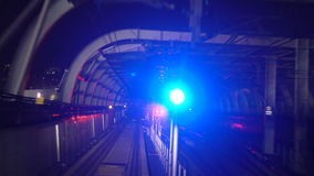 Outdoor Subway View. Night. Subway view as seen from a forward moving train. Passing outdoor structural frame tunnel with blue and red signal lights at night stock footage