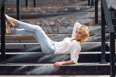 Outdoor summer fashion stunning portrait on pretty young blonde sexy woman dressed in a white shirt and torn jeans having fun in t. He street Stock Image