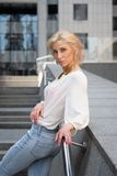 Outdoor summer fashion stunning portrait on pretty young blonde sexy woman dressed in a white shirt and torn jeans having fun in t. He street Stock Photo