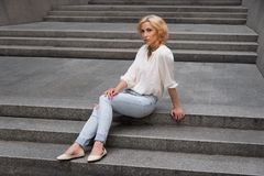 Outdoor summer fashion stunning portrait on pretty young blonde sexy woman dressed in a white shirt and torn jeans having fun in t. He street Stock Images