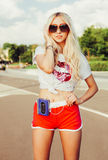 Outdoor summer fashion stylish portrait of young pretty sexy blonde girl posing in vinage sunglasses, T-shirt, shorts and listenin. Summer fashion stylish Stock Photos