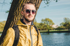 Outdoor summer lifestyle portrait of young bearded man looking away. Hipster style guy with sun glasses, dressed in Royalty Free Stock Images