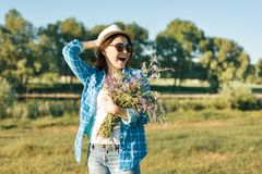Outdoor summer portrait of adult woman with bouquet of wildflowers, straw hat and sunglasses. Nature background, rural landscape, royalty free stock photos