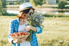 Outdoor summer portrait of adult woman with strawberries, bouquet of wildflowers, straw hat and sunglasses. Nature background,. Rural landscape, green meadow royalty free stock photography