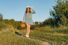 Outdoor summer portrait of girl teenager walking in rural country road in dress and hat with basket of strawberries. Nature. Background, rural landscape, green royalty free stock images