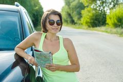 Outdoor summer portrait of mature woman with a map on the road near the car.  stock photography