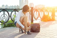 Outdoor summer portrait of mature woman in sunglasses with a bag and straightening shoes in the evening sunny city stock image