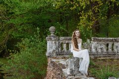 Free Outdoor Summer Portrait Of Young Pretty Cute Girl. Beautiful Woman Posing At Old Bridge.  In White Dess Siting Near Stone Railing. Royalty Free Stock Photography - 83757167