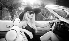 Outdoor summer portrait of stylish blonde vintage woman driving a convertible retro car. Fashionable attractive fair hair female with black hat in withe stock photography
