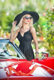 Outdoor summer portrait of stylish blonde vintage woman posing near red retro car. fashionable attractive fair hair female Stock Image
