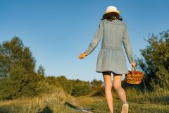 Outdoor summer portrait of teen girl with basket strawberries, straw hat. Girl on country road, back view. Nature background, royalty free stock images