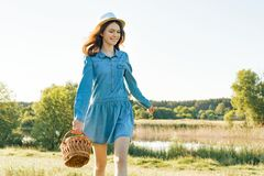 Outdoor summer portrait of teen girl with basket strawberries, straw hat. Nature background, rural landscape, green meadow, royalty free stock photos