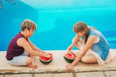 Outdoor summer portrait of two funny kids eating watermelon royalty free stock images