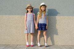 Outdoor summer portrait of two happy girl friends 7, 8 years holding hands. Girls in striped dresses, hats with backpack,. Background gray wall royalty free stock images