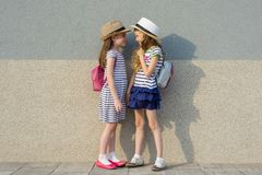 Outdoor summer portrait of two happy girl friends 7,8 years in profile talking and laughing. Girls in striped dresses, hats with. Backpack, background gray wall royalty free stock images