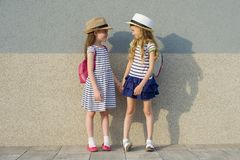 Outdoor summer portrait of two happy girl friends 7,8 years in profile talking and laughing. Girls in striped dresses, hats with. Backpack, background gray wall royalty free stock image