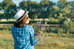 Outdoor summer portrait of woman with bouquet of wildflowers, straw hat. View from the back, nature background, rural landscape, royalty free stock images