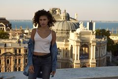 Outdoor summer portrait of young beautiful pretty girl posing in sunset lovely light and view on city roofs stock photos