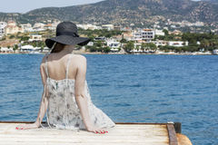 Outdoor summer portrait of young pretty woman looking at the sea in the port of Agios Nikolaos, enjoy her freedom and fresh air, w Royalty Free Stock Photo