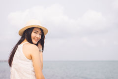 Outdoor summer portrait of young pretty woman looking to the ocean at tropical beach. Royalty Free Stock Photo