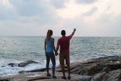 Outdoor summer portrait of young romantic couple in love posing at amazing stone beach, Stock Photo