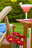Outdoor Summer Scene. Of a Deck Chair and Drink With Green Grass yard In The Background Royalty Free Stock Photos