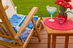 Outdoor Summer Scene. Of a Deck Chair and Drink With Green Grass yard In The Background Stock Images