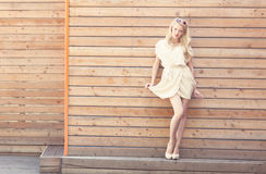 Outdoor summer sensual fashion portrait beautiful young blond woman lifts the edge of a white dress standing on the background of. Wooden planks Stock Photo