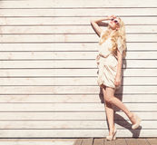 Outdoor summer sensual fashion portrait beautiful young blond woman a white dress standing on the background of wooden planks. Ton Stock Image