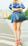 Outdoor summer smiling lifestyle portrait of pretty young woman with big blue handbag and hi heels shoes. Long blond hairs, blue o Stock Photo