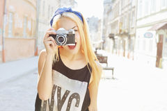 Outdoor summer smiling lifestyle portrait of pretty young woman having fun in the city in Europe with camera. Travel photo of phot. Ographer. Making pictures in stock images