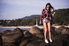 Outdoor summer stylish portrait of beautiful elegant woman with perfect fit body and long legs walking along on the Royalty Free Stock Photography