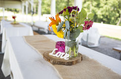 Outdoor Summer Wedding Reception. A rustic bouquet of bright flowers and burlap runner adorns a simple picnic table in preparation for a wedding reception.  This Royalty Free Stock Photos
