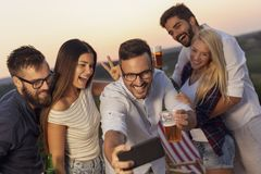 Outdoor summertime party selfie. Group of friends having fun at an outdoor summertime party, dancing, drinking beer and taking selfies royalty free stock image