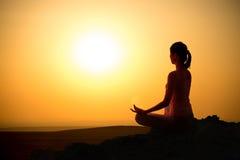 Outdoor sunrise yoga girl. Girl practicing yoga at sunrise, outdoor sun Stock Image