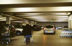 Outdoor supermarket witn senior man pushing shopping grocery car. FRANKFURT, GERMANY - DEC 21, 2016: Outdoor supermarket witn senior man pushing shopping grocery Royalty Free Stock Photos