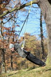 Outdoor suspension training in forest. Caucasian man at tree royalty free stock images