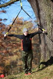 Outdoor suspension training in forest. Caucasian man at tree royalty free stock photos