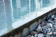 Outdoor swimming. Pool edge overflow drain stone Royalty Free Stock Photo