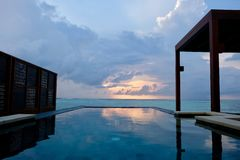 Outdoor swimming pool of Four Seasons Hotel in beautiful sunrise cloud in Maldive island resort royalty free stock images
