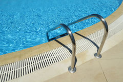 Outdoor swimming pool ladder. Grab bars metal ladder to a blue water pool royalty free stock image