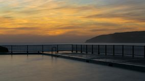Outdoor swimming pool by the ocean at dawn stock image