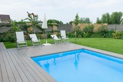 Outdoor swimming pool on private residence, lawn, garden. Stock Photos