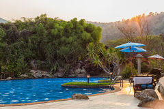Outdoor Swimming Pool in sunset time. Outdoor Swimming Pool with sunset behind mountain Stock Photo