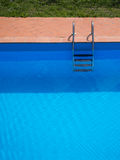 Outdoor swimming pool in sunshine. Vertical composition. Royalty Free Stock Photography