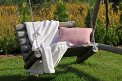 Outdoor swing. Wooden outdoor swing with blanket and pillow Royalty Free Stock Photo