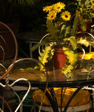 Outdoor Table. Quaint little table with yellow flowers stock image
