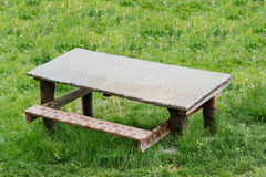 Outdoor table with a bench on green grass Stock Image