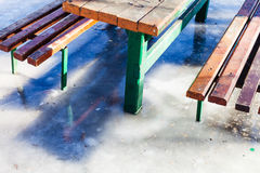 Outdoor table and benches frozen in puddle. In winter Stock Photos
