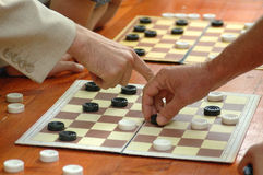 Outdoor table for checkers(draughts) game. People playing checkers game tournament at long wooden table with two boards made of paper visible with plastic pieces stock photo